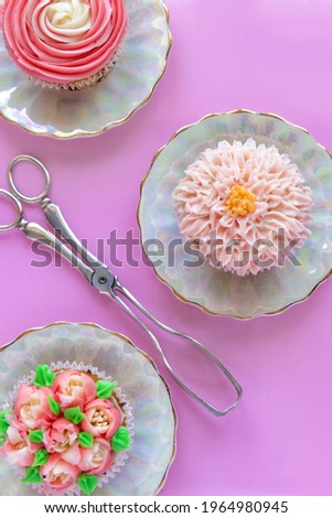colorful cup cakes decorated with icing on a pink background ideal for a cooking , teaching poster or backdrop