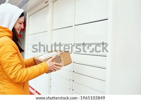 the girl sends the package to the mail in the parcel locker. Receiving package. The woman holds a box, looks at the package and smiles. orange jacket. Royalty-Free Stock Photo #1965103849
