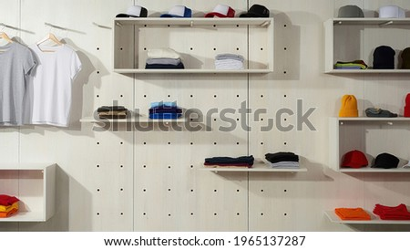 Collection of colorful cotton clothes laid out on the shelves in the store. Custom wear at clothing printing company. Web Banner