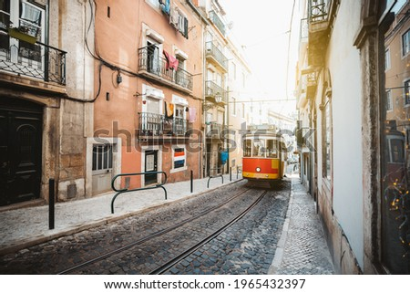 A wide-angle view of a red retro tram on a narrow street with one-way rail traffic in a European city; a vintage tourist streetcar in red and yellow colors on a tramway track over paving stone, Lisbon Royalty-Free Stock Photo #1965432397