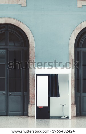Vertical shot of an indoor empty photo booth with open curtain, in between two wooden arch doors for creating photos for passport and documents with a blank template banner placeholder on a cabin wall