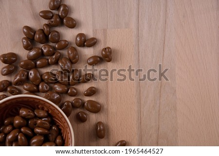 Raisins covered in chocolate on the table top view stock images. Raisins in chocolate on a wooden background stock photo