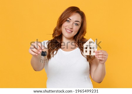 Smiling young redhead plus size body positive female woman girl 20s in white casual t-shirt posing hold in hands house bunch of keys looking camera isolated on yellow color background studio portrait Royalty-Free Stock Photo #1965499231
