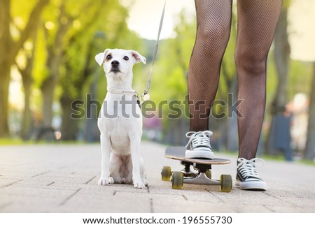 Close-up of legs of teenage girl on skateboard with her dog #196555730