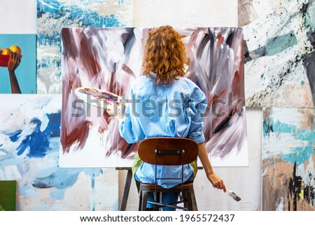Back view woman artist is drawing abstract picture in workshop studio gallery. Process of creating brown beige oil, watercolor, acrylic painting at creative workplace. Contemporary modern art concept.