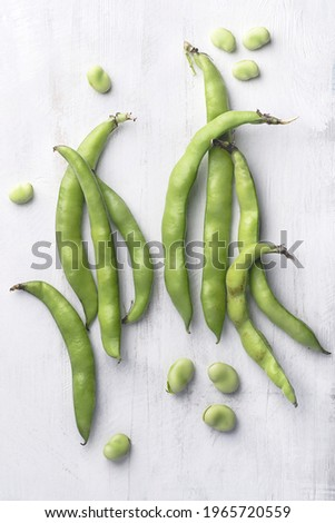 Broad bean or  fava beans (Fave) on the white wooden background, close-up.  From garden to table: springtime vegetables and legumes Royalty-Free Stock Photo #1965720559