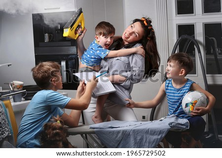 A very busy mother.A mother who does several things at the same time. Royalty-Free Stock Photo #1965729502