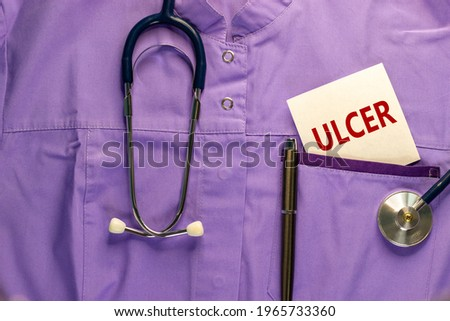 Stomach ulcer symbol. Medical uniform, white card with the word 'ulcer', metalic pen and stethoscope. Medical and stomach ulcer concept. Copy space.