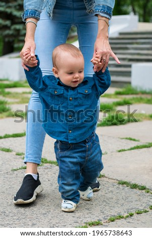 Baby's first steps. The first walk with mom's support by the arms, lifestyle. A one-year-old Caucasian boy and his young mother are walking, childhood, motherhood, first achievements. Royalty-Free Stock Photo #1965738643