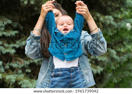 Mom raises her son's hands, have fun, play, laugh. A young Caucasian mother and her one year old son in stylish denim clothes. The concept of family values, maternal care, happiness, care. Royalty-Free Stock Photo #1965739042