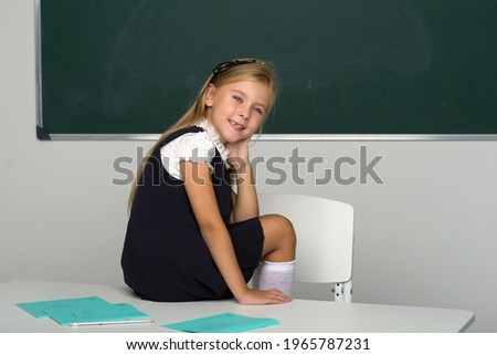 Adorable schoolgirl sitting on desk in classroom Royalty-Free Stock Photo #1965787231