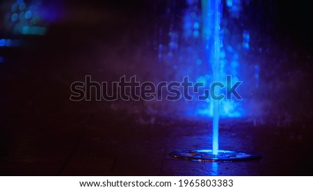Splashes of colorful fountain. Water illuminated in diverse colors falling on a fountain which change its water color in the night. Royalty-Free Stock Photo #1965803383