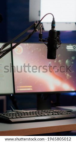 Empty streaming home studio equipped with professional equipment during online tournament late at night in gaming studio. Pro streamer playing space shooter video game having esport championship Royalty-Free Stock Photo #1965805012