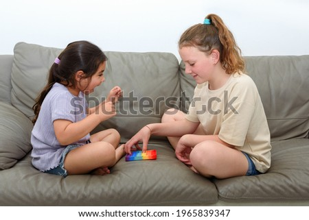 Two cute children playing with the Pop It fidget. One laughing girl raises hands in victory. Push pop bubble flexible fidget sensory toy provide discharge and are good for the development of kid. Royalty-Free Stock Photo #1965839347
