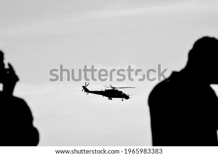 Helicopter in the sky and people silhouette, black and white photo