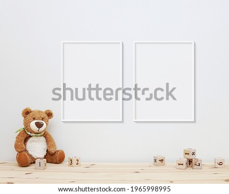 Two nursery frames mockup, 2 blank frames hanging on wall in baby room, soft toy bear and wooden blocks on shelf.