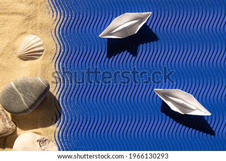 concept summer, vacation, two white boats on the blue paper waves, stones and shells on the sand,shadows, applique, abstraction background, wallpaper,flat lay