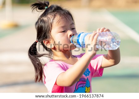 A 3-4 years old girl was drinking water to quench her thirst due to the hot weather. Kid sweat on their faces. Child drink cold water. Cute children wearing a pink shirt. In the summer or spring. Royalty-Free Stock Photo #1966137874