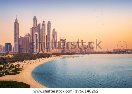 Sunset view of the Dubai Marina and JBR area and the famous Ferris Wheel and golden sand beaches in the Persian Gulf. Holidays and vacations in the UAE Royalty-Free Stock Photo #1966140262