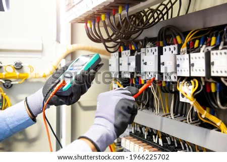 Electrical engineer using digital multi-meter measuring equipment to checking electric current voltage at circuit breaker and cable wiring system in main power distribution board. Royalty-Free Stock Photo #1966225702