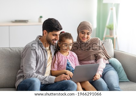 Young muslim parents and girl using laptop together at home, surfing internet or having video chat with someone, sittig on sofa. Happy arab man, child and woman in hijab staying home on isolation Royalty-Free Stock Photo #1966291066