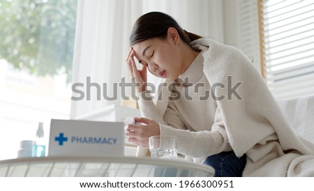 Sick asian woman sit under blanket acute severe headache on sofa at home. Female hold or check drug medicine capsule at home, suffer from flu. Cold or fever side effect after Covid19 vaccine shot. Royalty-Free Stock Photo #1966300951