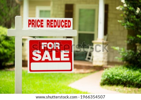 House for sale, price reduced. Real estate sign. Front yard