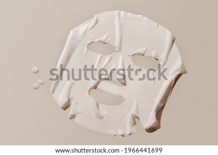 facial sheet mask on brown background.  Royalty-Free Stock Photo #1966441699