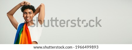 Gay man in crop top posing on white background with copy space. Man with a lgbtq flag on his shoulder looking away.