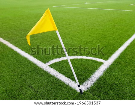 Yellow flag on the corner of a football field. Place for a corner kick on a soccer ball. White line marking sports field for football players. Royalty-Free Stock Photo #1966501537