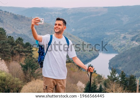 young man hiking or hiking taking pictures with mobile phone