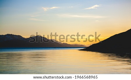 Beautiful landscape picture along the coast in Alta, Norway. The photo was taken in the summer under the midnight sun with beautiful mountains in the background of the sea.