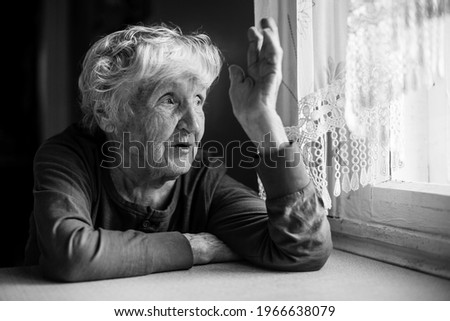 An old woman talking gesticulating at the table. Black and white photo.