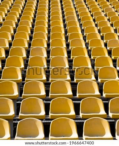 empty seats. modern stadium. yellow tribunes. seats of tribune on sport stadium. Royalty-Free Stock Photo #1966647400