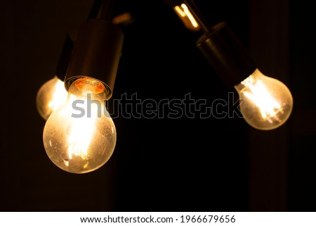 Macro shot of isolated interior light bulb against dark background. It is a chandelier that hangs from a two story sunroom. Over times as home have become more modern, this has become popular.