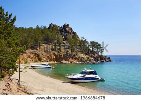 The beautiful sandy beach on summer sunny day. Yachts near the shore. Lake Baikal, the Sandy Bay. . High quality photo