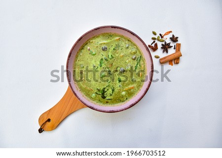 THai Green beef,Green curry, Thai green curry with beef chilli and eggplant garnished with slice fresh chilli and Basil leaf in black colour bowl on white background with spicy.