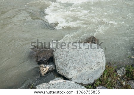 Minimalist mountain scenery with rapids of fast turbulent river. Beautiful mountain landscape with powerful mountain creek with stones and boulders. Minimal scenic nature background of mountain river. Royalty-Free Stock Photo #1966735855