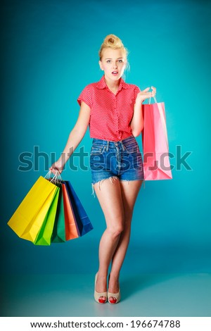 Pinup girl young woman in retro style buying clothes. Client holding colorful shopping bags on vibrant blue. Retail and sale. Studio shot. #196674788
