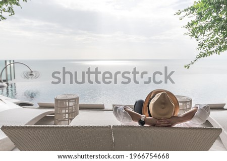Relaxation holiday vacation of businessman take it easy for work-life balance resting happily on beach chair at swimming pool poolside beachfront resort hotel with summer sea sky ocean view background Royalty-Free Stock Photo #1966754668
