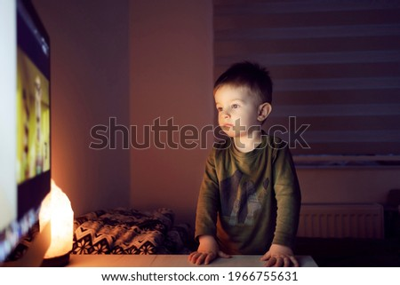 A boy watching cartoons on television. The boy is standing in a closed room in front of the TV and leaning on a table staring at a cartoon. Occupation before bed, cartoon for good night Royalty-Free Stock Photo #1966755631