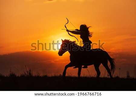 silhouette of a woman like an Indian riding a horse and shooting from a bow Royalty-Free Stock Photo #1966766716