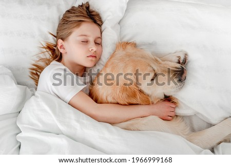Beautiful little girl staying in the bed with golden retriever dog in the morning time and napping. Kid sleeping with pet at home. Portrait of friendship between human child and animal Royalty-Free Stock Photo #1966999168