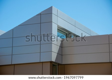 The exterior wall of a contemporary commercial style building with aluminum metal composite panels and glass windows. The futuristic building has engineered diagonal cladding steel frame panels. Royalty-Free Stock Photo #1967097799
