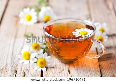 cup of tea with chamomile flowers on rustic wooden background #196710491