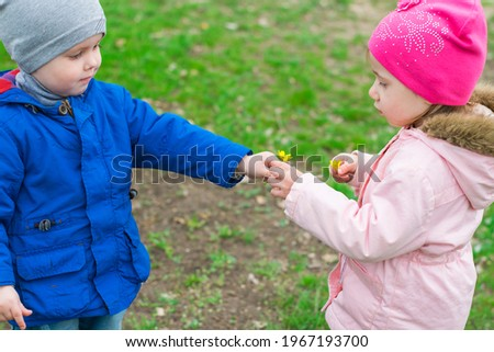 A cute boy of 2-3 years old gives a girl a yellow spring flower. The concept of a happy childhood, friendship, love, sympathy. Royalty-Free Stock Photo #1967193700