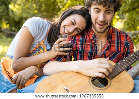 Couple hangout in the countryside drinking red wine, singing, playing guitar, embracing and having fun together sitting in the park.