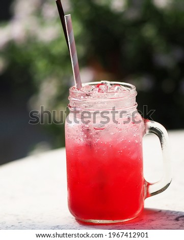 Red lemon soda water flavoured drink, Cool Drinks Beverages with ice in clear glass with paper and plastic straws on white table Royalty-Free Stock Photo #1967412901