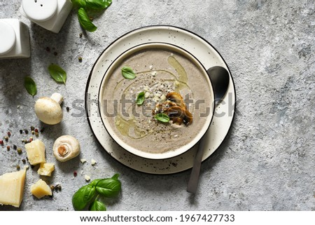 Soup puree with mushrooms and parmesan on a concrete kitchen table.Top view. Royalty-Free Stock Photo #1967427733