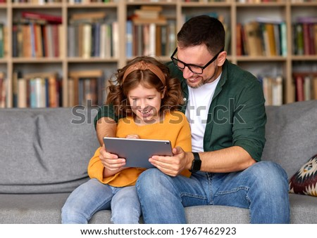 Young loving father taking care of daughter at home, little girl watching funny video or cartoons on digital tablet with dad while sitting on sofa. Children and modern technologies concept